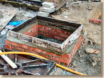 'regulating brickwork' from the web at 'http://www.pavingexpert.com/images/features/manhole_frame_bedded.jpg'