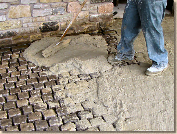 spreading wet grout over setts