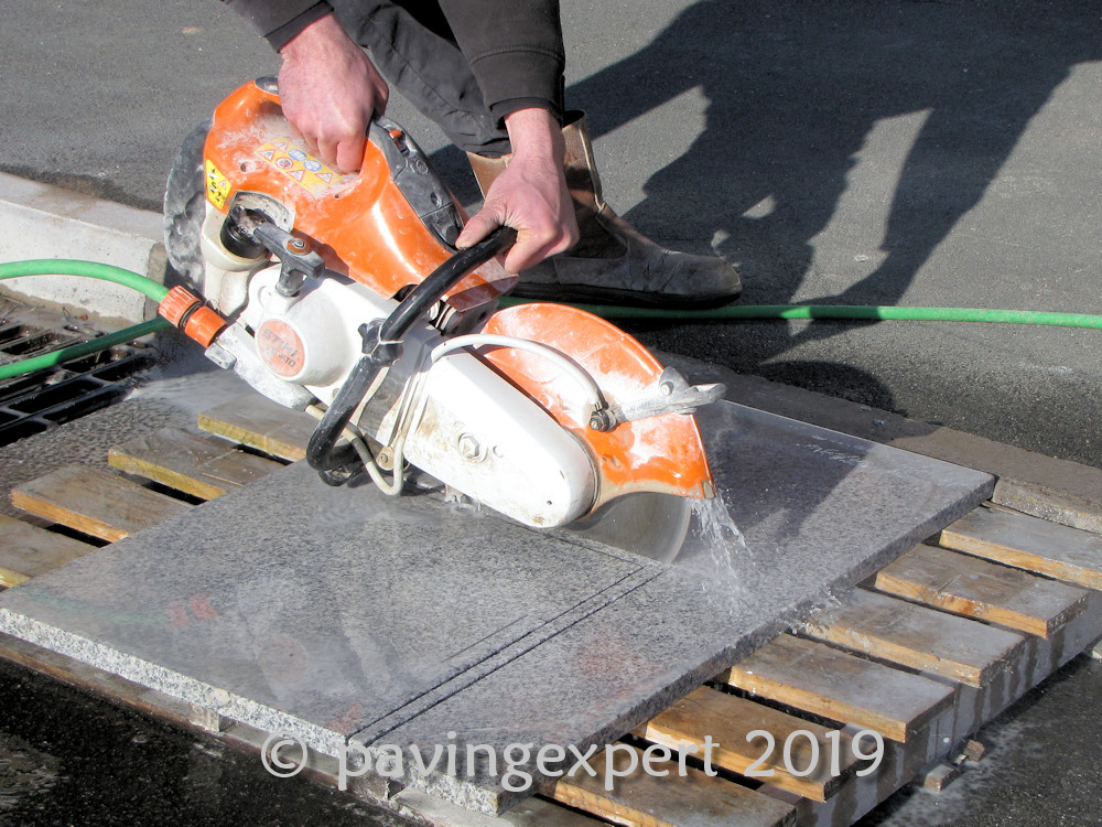 hand held saw cutting paving